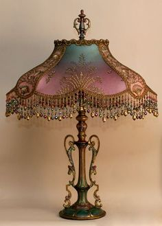 Antique 1920s era metal lamp base has been hand-painted. Hand-dyed Turkish Starling silk lampshade, dyed from pale teal into deep mauve and covered on the sides with gold metallic net with turquoise swirls.