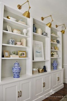 Cabinets below, shelves above, accent color behind, sconces to light