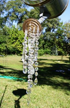 My neighbor and good friend, Debra, made this wonderful garden decoration from an old watering can and chandelier crystals. The light from the sun reflects off