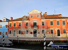 Photo taken on the island of Burano in the village of fishermen and lace embroiderers in the municipality of Venice Italy. In the picture you see, over the channel on which there are two boats in the foreground, a large manor house illuminated by the setting sun and colored light red, a color that was ruined in time at the base.