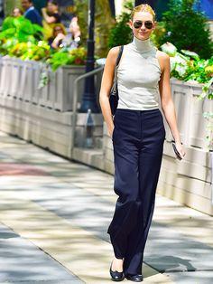 Karlie Kloss wears a turtleneck tank top, high-waisted wide leg pants, ballet flats, and aviator sunglasses