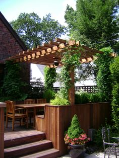 Backyard deck with a wooden tent and plants.