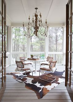 Creative Juices Decor: How to Decorate Using Animal Hides - Brown and White hide on porch - added sheepskin over chairs. Lots of texture - fun space
