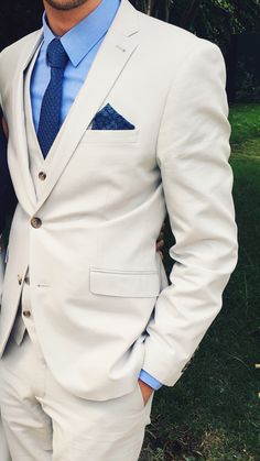 Men's wedding suit. Cream linen style suit. Pale blue shirt and dark blue tie.