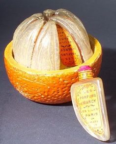 Today's museum moment is this 1925 perfume presentation by De Marcy, fittingly called L'Orange Variee. It came complete as a peeled orange of painted composition, holding 8 glass bottles with labels.