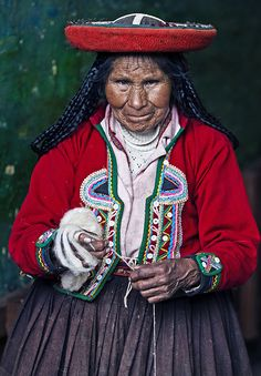 Quechua woman winding handspun yarn on her hand, preparing to ply