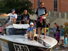 The crew of JP Larkin, Ecolab Power Boats and Race Team participating in the power boat parade through downtown Pensacola Saturday evening toss trinkets to bystanders as they move through downtown Pensacola.  #ThunderRun-#Super-Boat Grand Prix in #PensacolaBay.