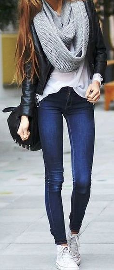 Woman wearing dark blue jeans and white Converse trainers