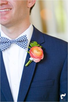 Groom in Navy Tux with Checked bowtie and Coral Boutonniere   Florals by: Isn't She Lovely Florals.