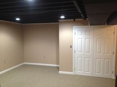 This exposed basement ceiling was spray painted black due to the duct work and pipes to create a visually higher ceiling. This was a great idea when you're dealing with pipes and duct work and the end result is very sharp looking basement.