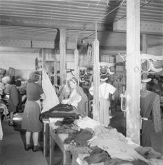 LIBERATION BERGEN-BELSEN CONCENTRATION CAMP MAY 1945 (BU 6365) Women at Belsen selecting new items of clothing from supplies provided by UNRRA and by a levy on the local population. Mrs H Tanner, an UNRRA relief worker from Grantham, assists inmates select a dress.