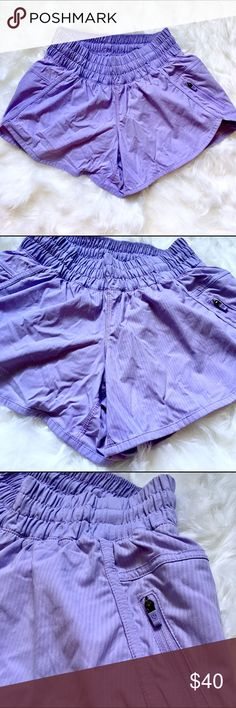 Lululemon Purple Shorts Lulu purple shorts. High waisted and elastic waistband. 3 inch inseam. Light lilac purple color. It's lighter than in the pics, just bad lighting. Loose fit (as in not like body hugging spandex type). Built in underwear. Elastic at the waistband. Excellent condition/ only worn a handful of times but too small on me. Small patch of fading as seen in the last picture but not noticeable when wearing 😊😊 side zipper lululemon athletica Shorts