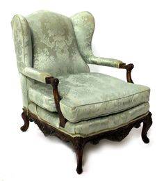 An early 20th century mahogany framed wingback armchair with carved open arms and shaped frieze on scroll supports.