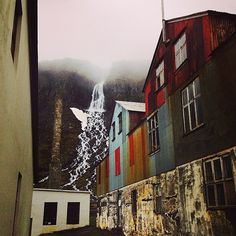 A beautiful waterfall flowing behind a deserted herring factory in Djúpavik in the Westfjords in Iceland.