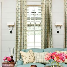 Hang curtains wide and high over a window casing to visually enlarge the space and add height to any room.