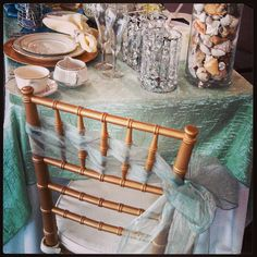 @allpropartyconsultantss photo: North Georgia Party Rental showroom. Teal champagne crush iridescent topper, gold chivari chair with sea foam organza sash. Set up provided by all pro party consultants.