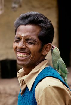 Steve McCurry: India. 1978. A man laughs while a parrot bites his ear.
