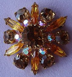 This fabulous brooch has a gorgeous flower head design. It has a goldtone metal frame adorned with shimmering round-cut and marquise-cut amber, topaz and aurora borealis glass stones.