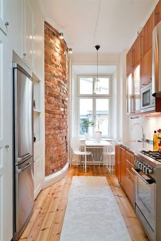 Love the exposed brick and the alley kitchen. A fresh look- excellent lighting as well!