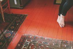 Red painted wood floor + old rugs - by Olivia Rae James, via Flickr