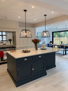 This stunning kitchen installation features light grey hand-painted cabinets with various larder tops, perfect for storing small appliances and larger food items. The contrasting dark blue island with white worktops and statement pendant lighting, along with mirrored splashback, creates a modern multi-functional family space #greykitchen #bluekitchenisland Dark Blue Kitchen Cabinets, Dark Blue Kitchens, Blue Kitchen Island, Gray And White Kitchen, Kitchen Cabinet Colors, Kitchen Island Lighting Uk, White Kitchen Worktop, Kitchen Worktops, Open Plan Kitchen Dining Living