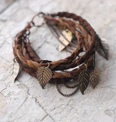 With a bohemian flair, this bracelet is made of brown leather braids and adorned with small leaf charms in silver, pewter and rustic gold.
