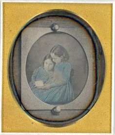 1840's 1/6 Plate daguerreotype of a daguerreotype of two little girls  reading. It was tacked to a piece of wood. You can clearnly see the  grain in the wood as well as the large tacks that held it on