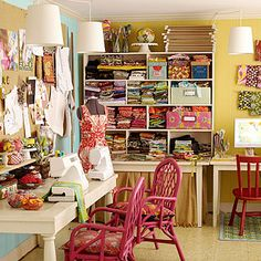 In fabric designer Anna Maria Horner's crafts room, multiple tables line the perimeter for lots of extra work space. One table gets skirted to hide more supply storage. Corkboard hangs on the wall above the work area for a place to tack magazine clippings, fabrics, and sketches. A cubby unit placed on a table gets fabric storage up to eye level. Plenty of task lighting hangs above all work areas.