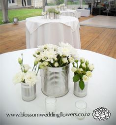 Wedding reception centerpiece arrangement of silver tin cans filled with white blooms, surrounded by tea light candles