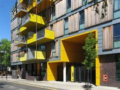 The timber cladding is applied in horizontal bands for each storey, helping to break down the scale to a human one. The bright yellow cladding further helps to add visual interest, and to also signal the entrance's location clearly within the street.