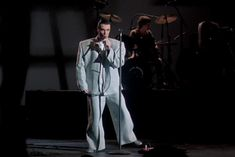 I'd use spot lights to light up the models as they perform on stage and the background would be dark - props instruments and microphones - although the movie featured a male lead singer the photo shoot would have only female models.  This pic of David Byrne from movie.