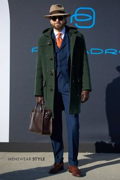 in Florence This stylish gentleman was spotted at Pitti Uomo wearing a beige fedora, orange tie and green duffle coat.A Clockwork Orange A Clockwork Orange may refer to: Mens Duffle Coat, Suit Combinations, Orange Tie, Neue Outfits, Winter Outfits Men, Elegant Man, Mens Attire, Green Coat, Messenger Bag Men