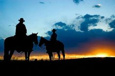 Beautiful sunset with two men riding horses