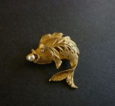 Vintage Brooch Gold Tone Fish Figural with Pearl    Beautiful fish figural brooch in a textured gold tone metal with a clear rhinestone eye holding a pearl in its mouth.    Measurements:    3.5 cm (1.37 inch) x 3.5 cm (1.37 inch)    Condition: Excellent