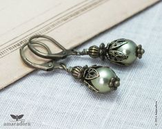 These dainty Edwardian inspired earrings feature quality Swarovski Crystal Pearls* in Light Green combined with bronze plated beads and findings.