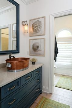 Copper sink with blue cabinets - subtle pairing of orange and blue.