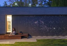 Architect Janna Levitt laser-cut an astral pattern into the garage door of this renovated Toronto home, installing LED lights behind the fiber-cement surface to complete her depiction of the constellations Sagittarius and Scorpio.