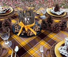 Outdoor tablescape with natural elements like pine cones, twigs, and scorns.... not sure if I like all the yellow and the tablecloth though...