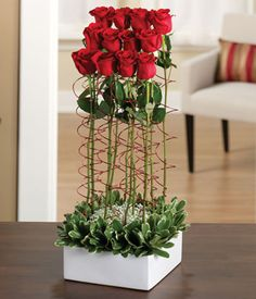 Dozen roses presented in a square container.