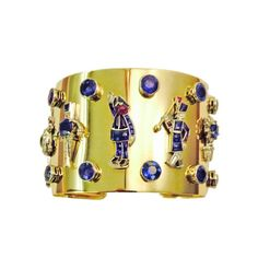 Bracelet in yellow gold and platinum set with art deco charms set with diamonds, emeralds and Montana sapphires, circa 1940.