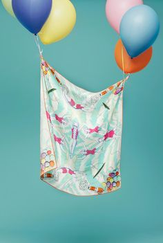 Great prop styling! Colorful balloons hold up a printed silk scarf.