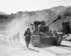 Men of the U.S. 7th Regiment, Third Division, plod along dusty Korean road alongside lumbering tank during field maneuver on Oct. 11, 1953. Although the fighting has halted, the United Nations troops in Korea are continuing their battle training. (AP Photo/Gene Smith)