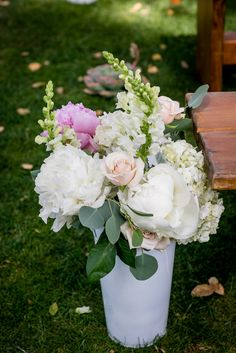 Galvanized vases overflowing with lush romantic florals like peonies, garden roses and hydrangeas and shades of pink, ivory and white lined the ceremony aisles, injecting the wooden benches with elegance and vibrancy.