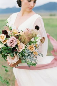 "From the editorial ""Elegant Montana Wedding Inspiration Dressed in Peach and Blackberry Tones."" Anselmi Floral Design absolutely took our breath away with her organic arrangements, complete with roses and wildflowers galore! Photography: @troymeiklephoto #stylemepretty #weddingbouquet #bridebouquet #weddingflowers #montanawedding #prettybouquet"