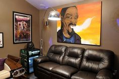 This custom painting provides the perfect finishing touch for hip-hop mogul Snoop Dogg's new cave. This side of the room features a plush leather couch flanked by a mini fridge and various memorabilia.