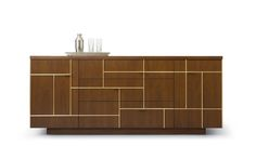 Fretwork by Altura features a lattice-like geometric grid of metal inlay overlaying the door and drawer faces. Integral pulls within the grid jut out at each grasp point. The Fretwork is available in two configurations, three standard sizes, all standard wood finishes and three metal finishes.