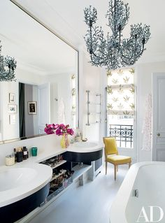 A seaweed-motif chandelier from Le Prince Jardinier adds a flamboyant note to Christian Dior executive Mathilde Favier-Meyer's Paris master bath, which has a counter and tub surround made of Corian.