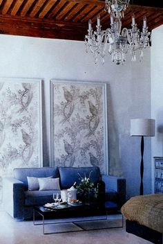 Wallpaper panels as art. love the blue sofa too and the wood beam ceiling!!