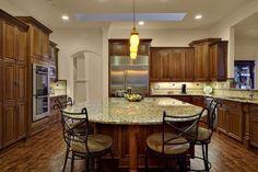 Mediterranean Kitchen with Raised panel, Skylight, Ms international amber yellow granite, Limestone Tile, Undermount sink