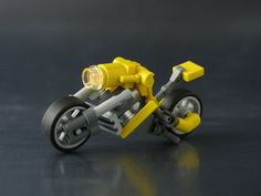 Amazing tiny scale Lego motorcycle, by Brian Kescenovitz. Crazy techniques in here. Did you notice the minifig arms as the rear wheel struts?